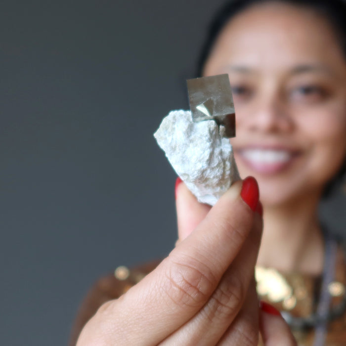 sheila of satin crystals holding pyrite cube on white matrix