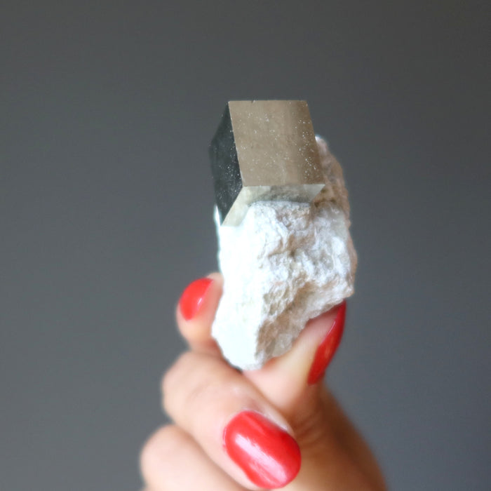 hand holding pyrite cube on white matrix to show reflective surfaces