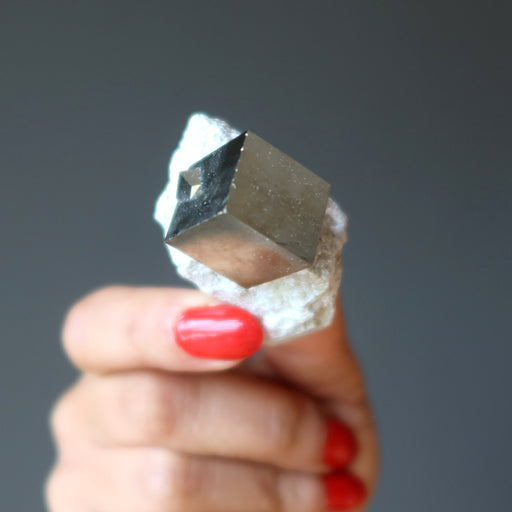 hand holding pyrite cube on white matrix