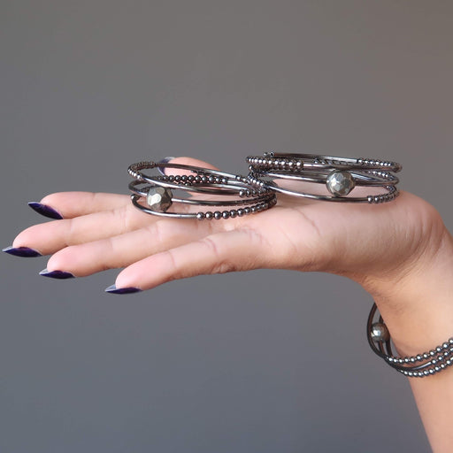 hand holding and wearing faceted pyrite on 3 coils of gunmetal beaded memory wire bracelets