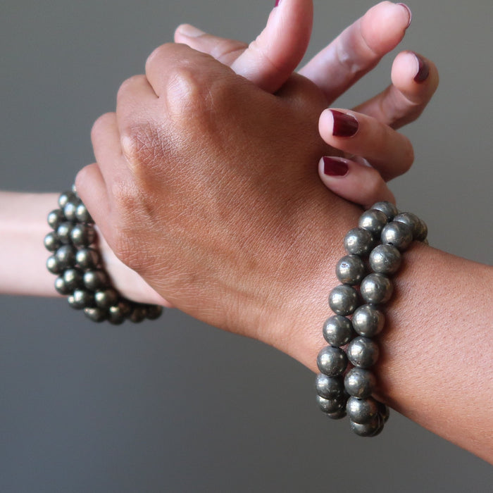 man and woman's hands clasping wearing pyrite bracelets