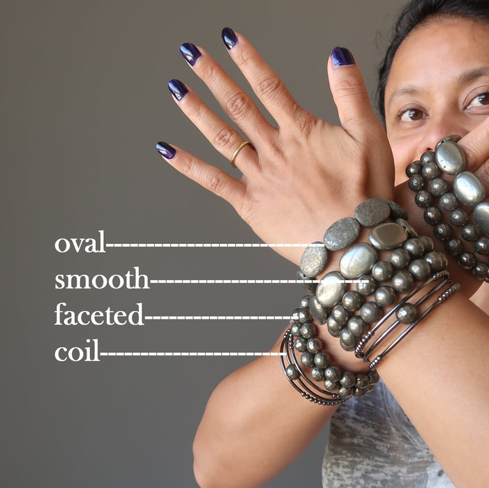 sheila of satin crystals with two hands stacked with different types of pyrite bracelets