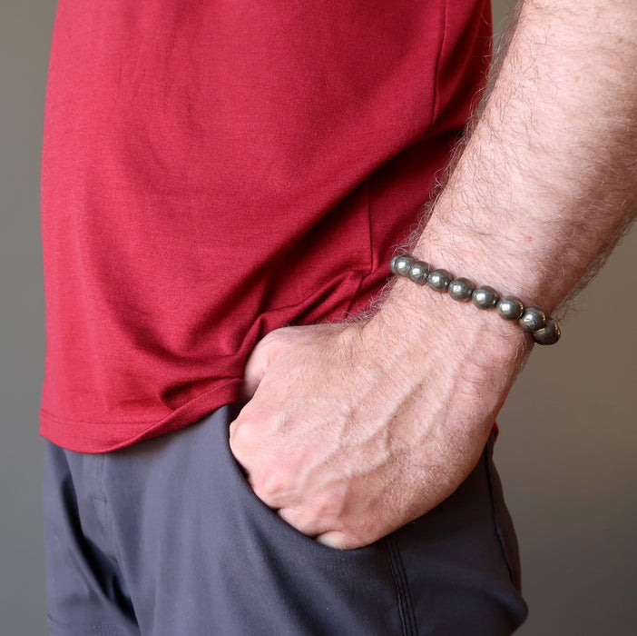 mans hand in pocket wearing round pyrite beaded stretch bracelet