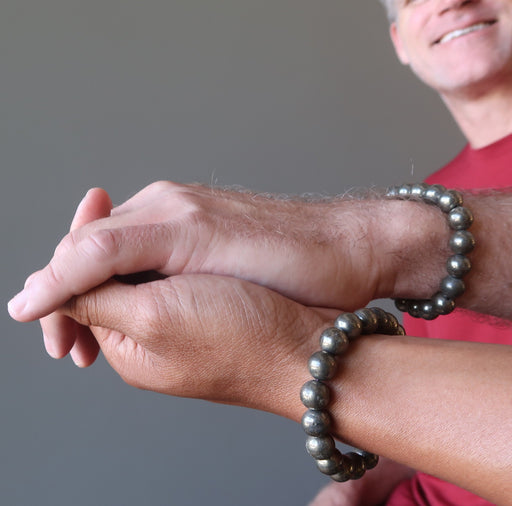 mens hands clasping wearing round pyrite beaded stretch bracelets