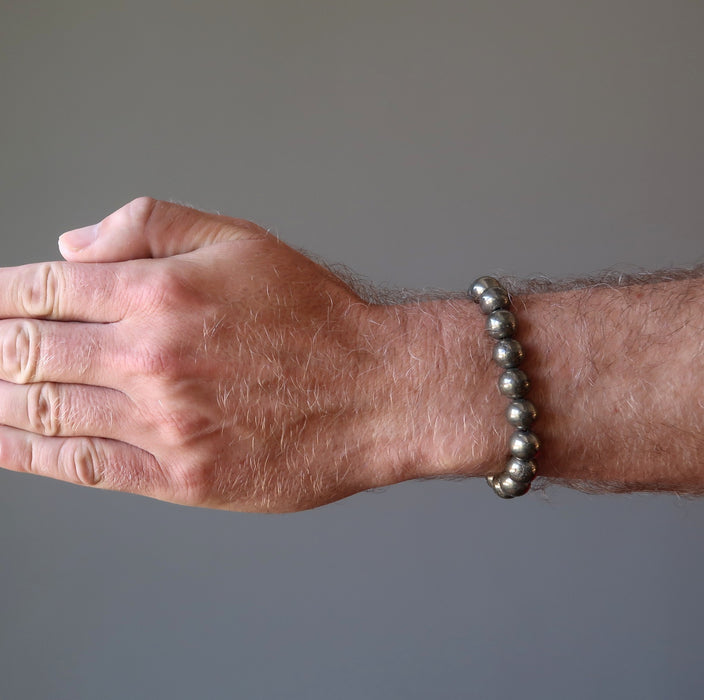 mans hand wearing round pyrite beaded stretch bracelet