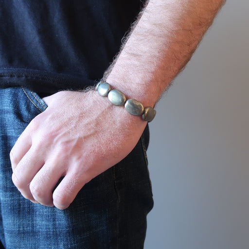 man hand in jeans pocket wearing pyrite oval stretch bracelet