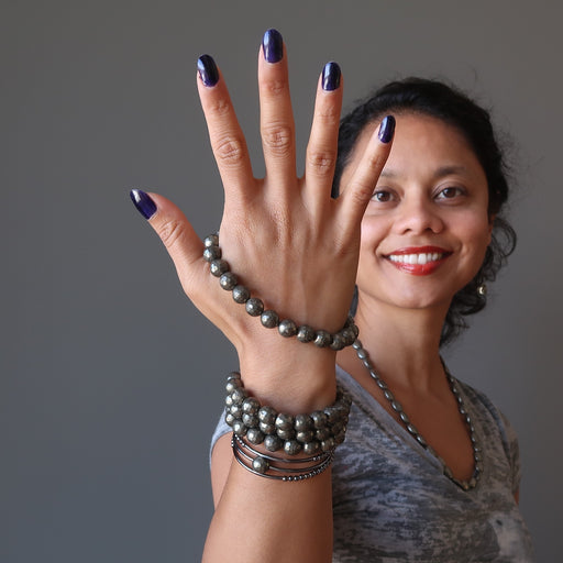 Sheila Satin of Satin Crystals wears faceted Pyrite bracelets on her hand while smiling