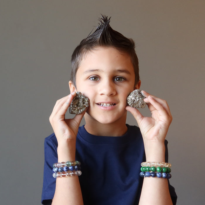 male kid holding two raw pyrite clusters