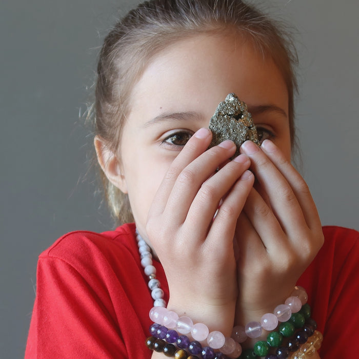 female kid with pyrite cluster at her third eye