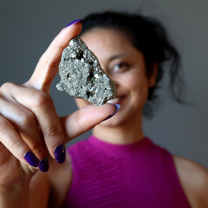 sheila of satin crystals holding raw pyrite cluster
