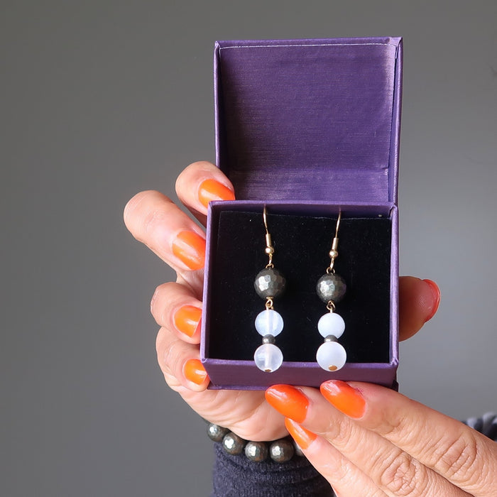hands holding satin crystals gift box with faceted pyrite and white selenite dangle earrings