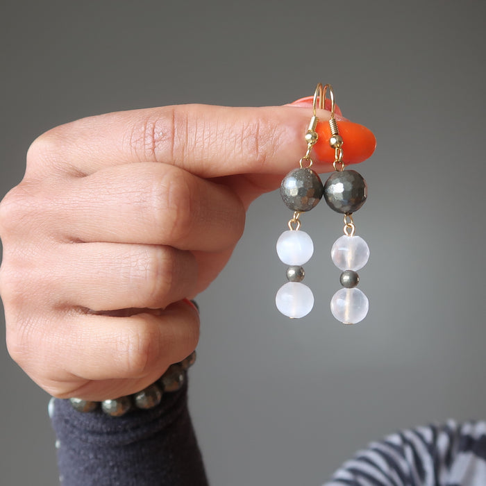 hands holding faceted pyrite and white selenite dangle earrings