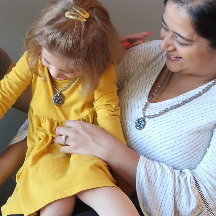 mother tickling daughter wearing matching pyrite rose necklaces