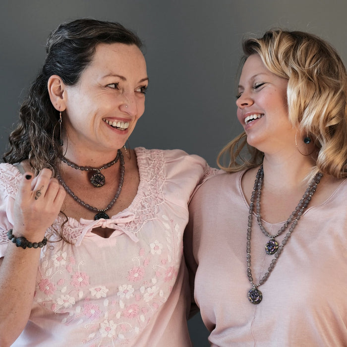 two friends laughing together wearing matching pyrite rose necklaces