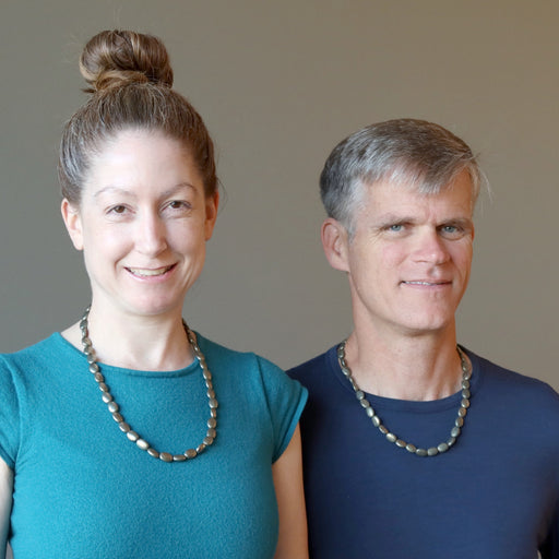 man and woman wearing pyrite oval necklaces