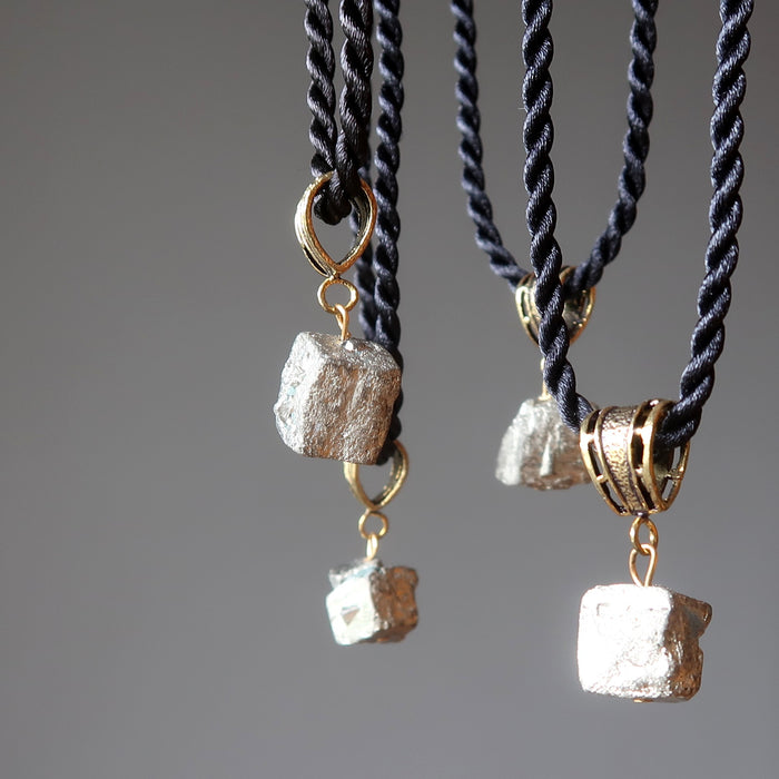 4 raw pyrite nuggets on black twisted necklaces