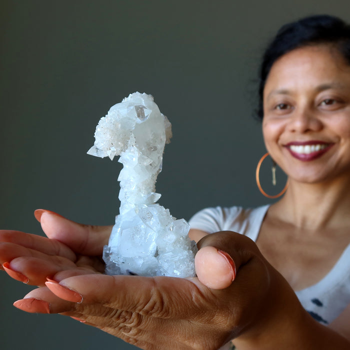 sheila of satin crystals holding a white clear quartz stalagmite cluster