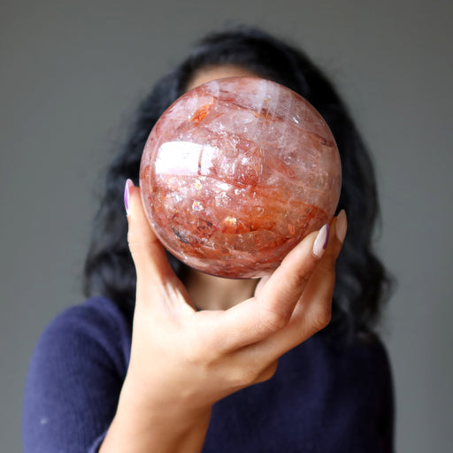 female model holding a red quartz sphere in front of her face
