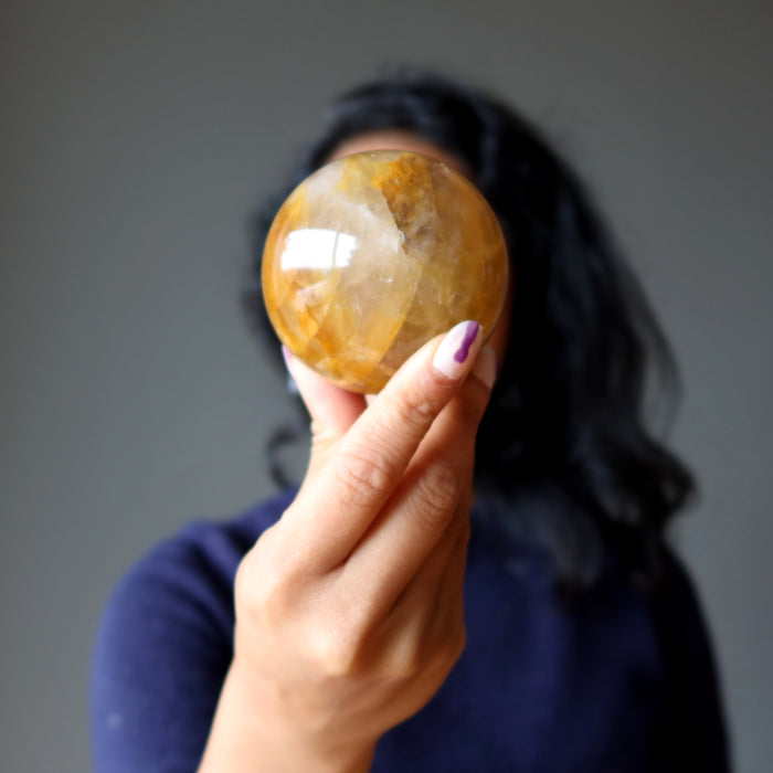 hand holding a golden quartz sphere