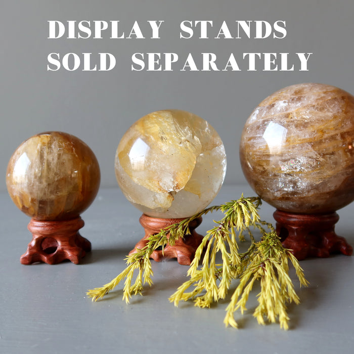 three golden quartz spheres on wood display stands and a sprig of pine