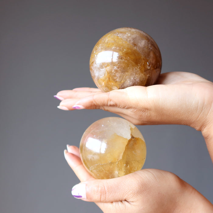hands holding 2 golden quartz sphere