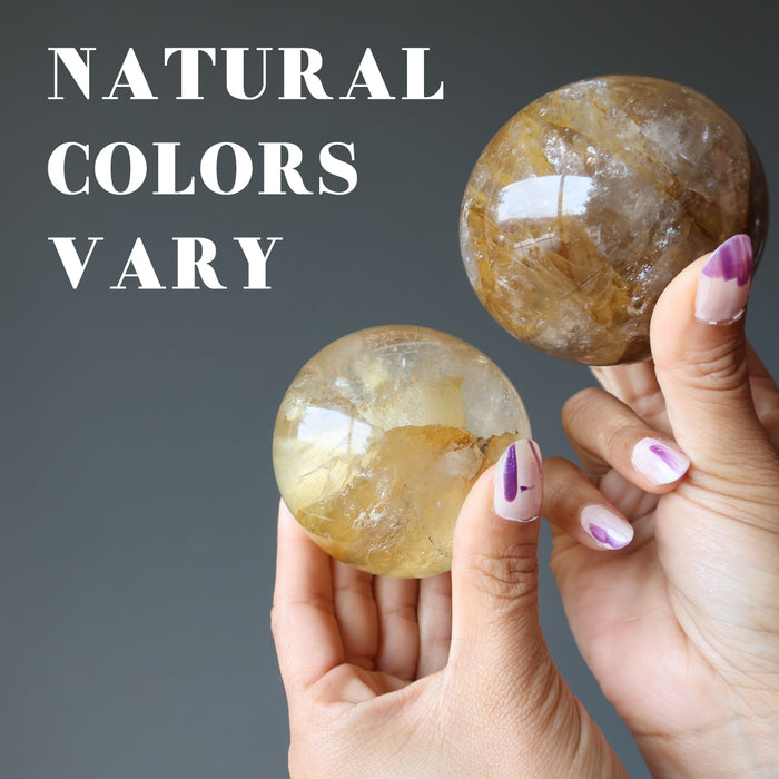 two golden quartz spheres showing natural colors vary