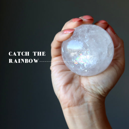 hand holding a quartz sphere showing rainbow inclusions
