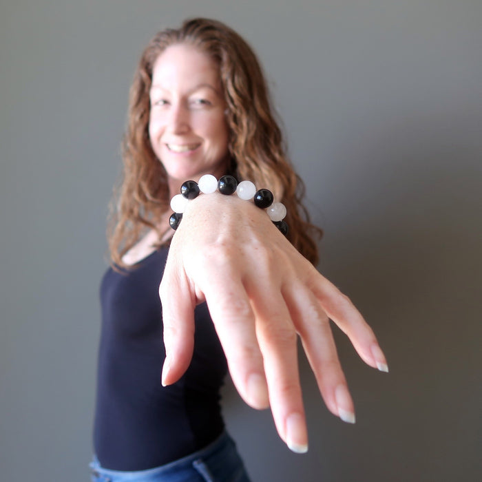jamie of satin crystals with hand outstretched wearing white quartz and black obsidian round beaded stretch bracelet