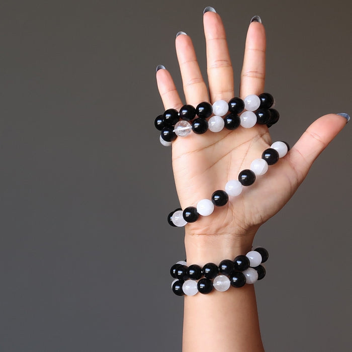 5 white quartz and black obsidian round beaded stretch bracelets on woman's hand