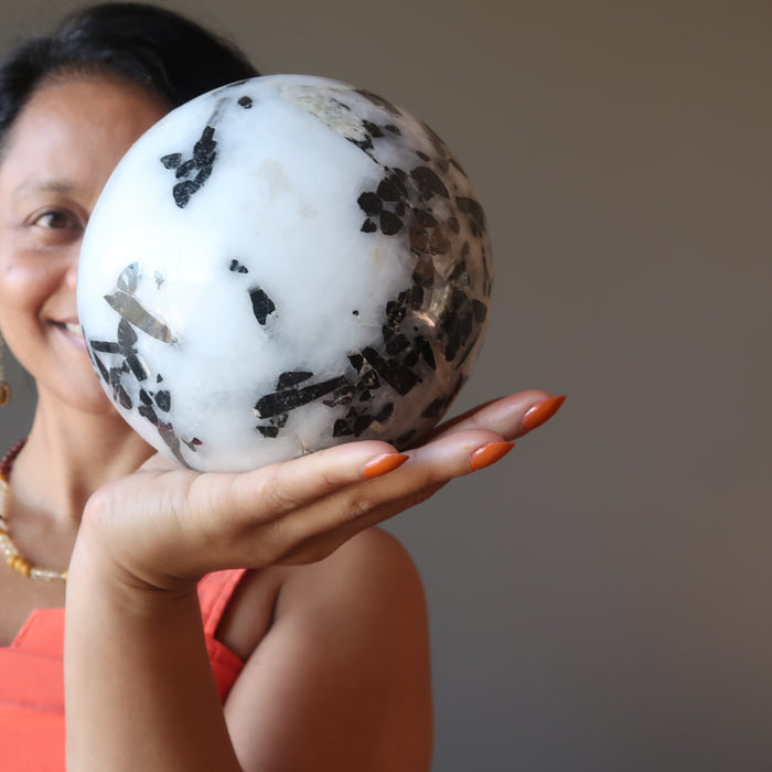 sheila of satin crystals holding a large tourmalinated quartz sphere