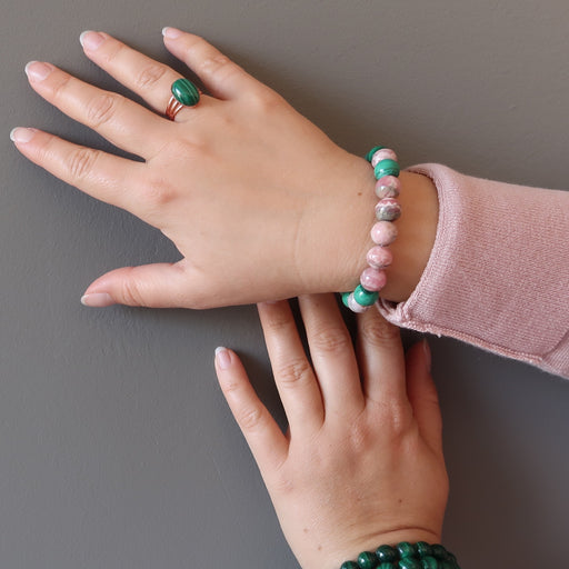 hand wearing rhodochrosite and malachite stretch bracelet and a malachite copper ring