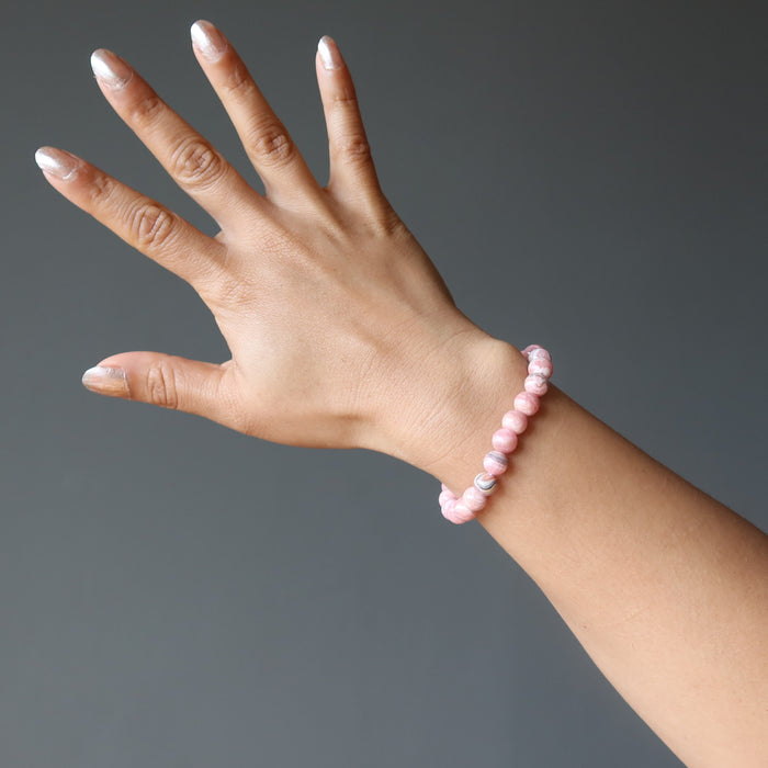 hand wearing rhodochrosite round beaded stretch bracelet