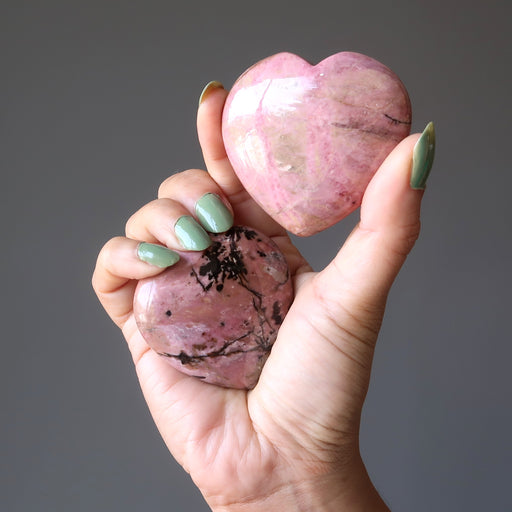 hand holding a pair of rhodonite hearts