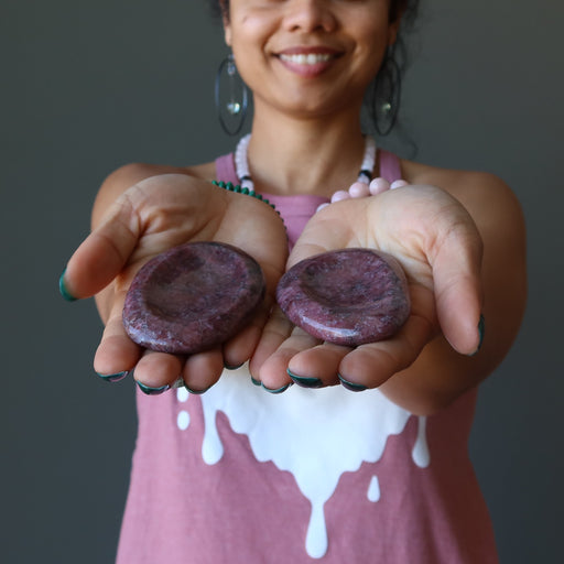 pink rhodonite worry stones in palms