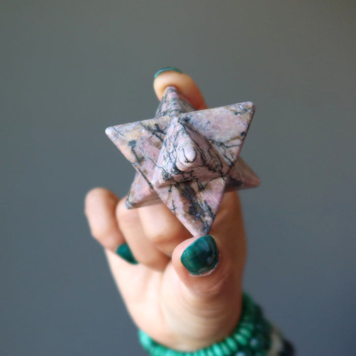 hand holding pink and black rhodonite merkaba