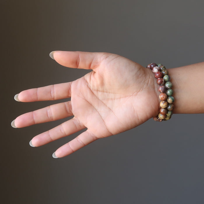 red and green tropical rhyollite bracelet pair being modeled on a hand