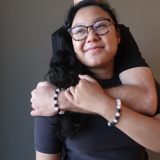 man embracing woman as they wear matching rose quartz lava bracelets