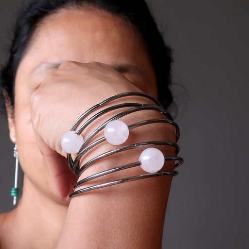 7 layer gunmetal bracelet with three statement beads in pink rose quartz being modeled on a woman