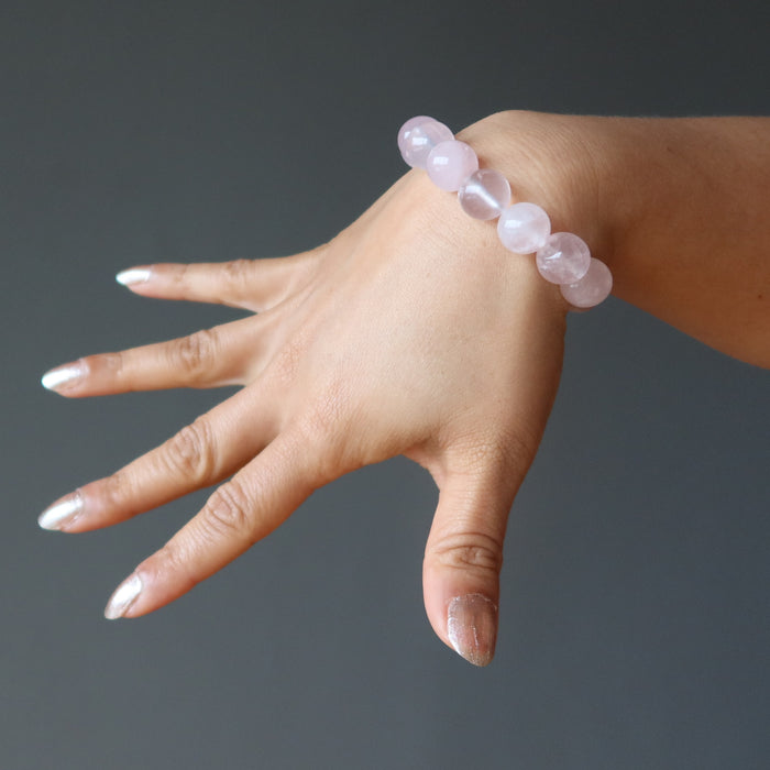 hand wearing clear pink rose quartz round beaded stretch bracelet