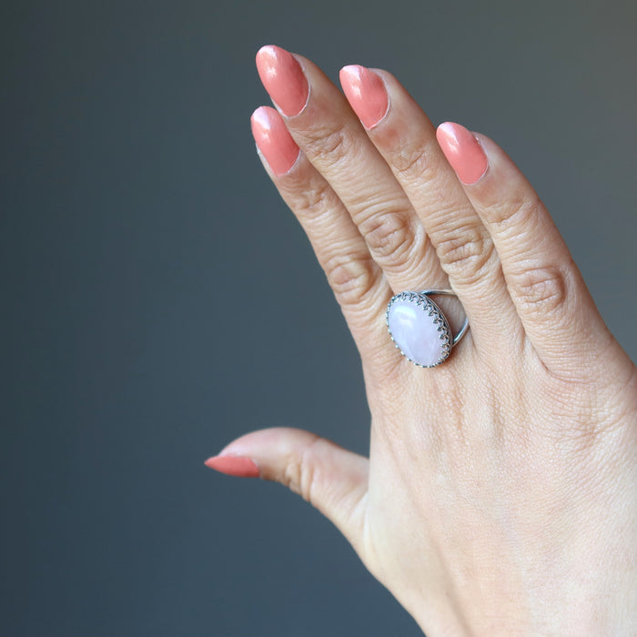 female hand wearing pink rose quartz oval in sterling silver adjustable ring