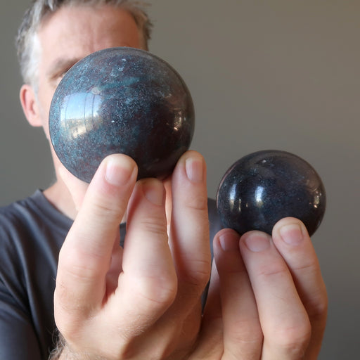 male model holding two ruby kyanite spheres