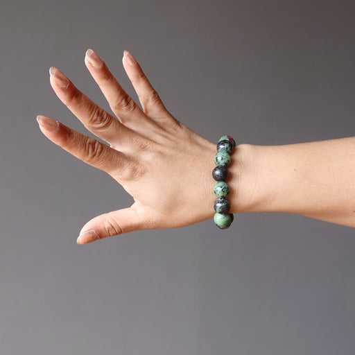 hand wearing ruby zoisite round stretch bracelet