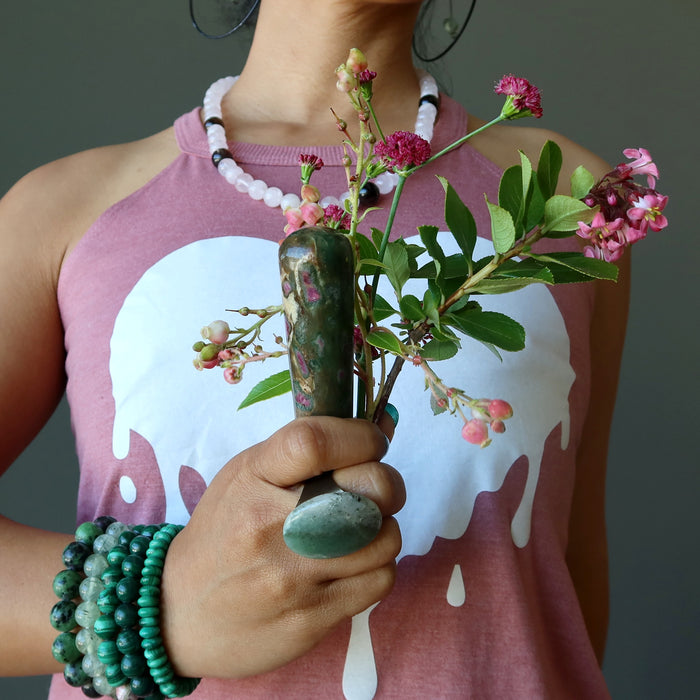 hand holding ruby zoisite tapered massage wand with pink flowers at the heart chakra