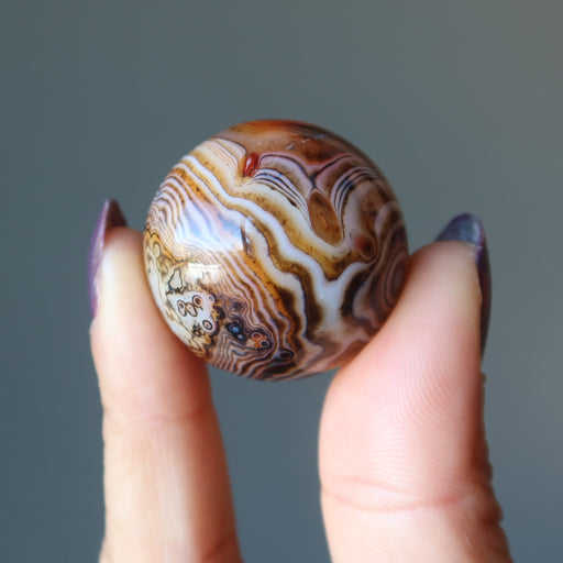 hands holding up a sardonyx sphere