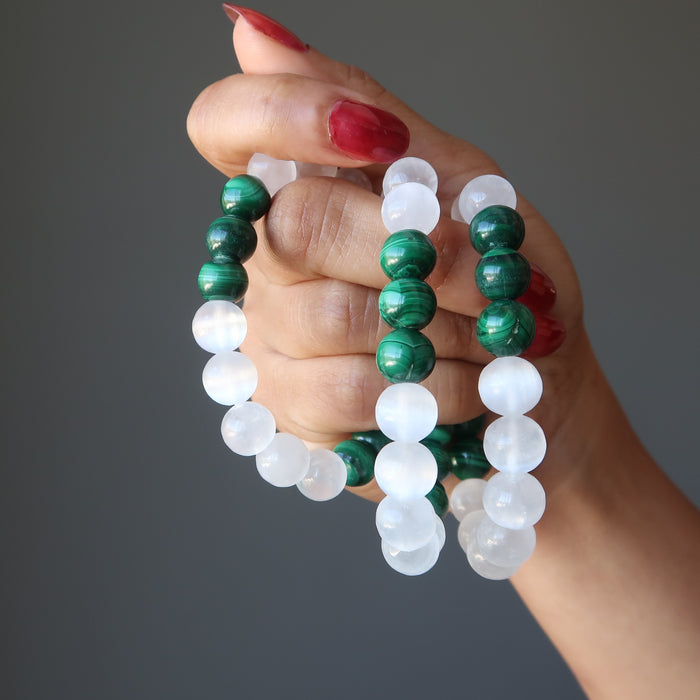three green malachite and white selenite bead bracelets being held in the hand of lady