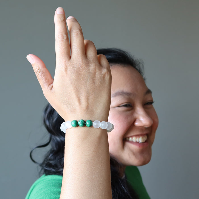 smiling model raises her hand to display selenite and malachite gemstone stretch bracelet