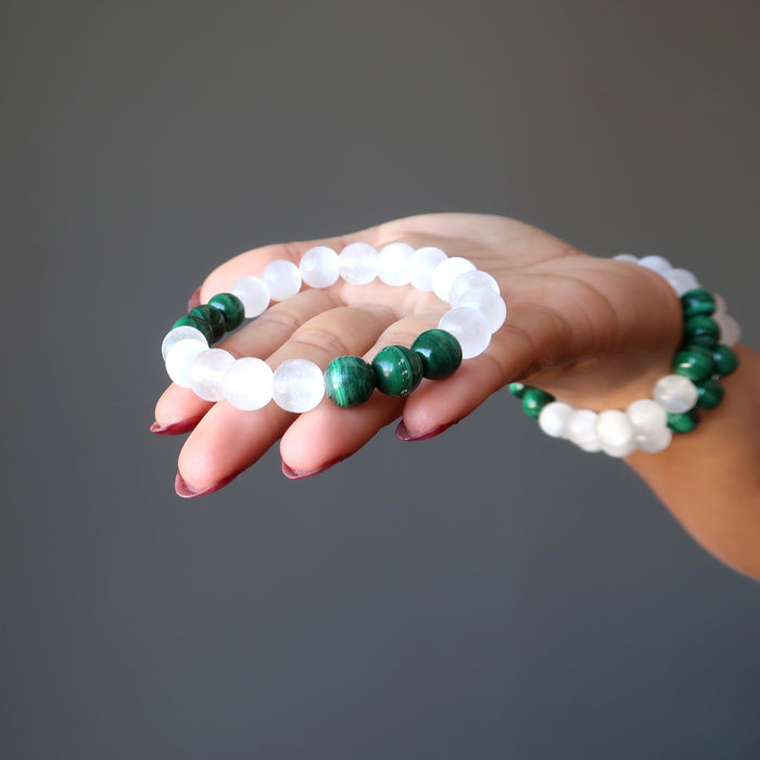 bright white selenite and green malachite bracelet in the palm of a woman's hand and two on her wrist