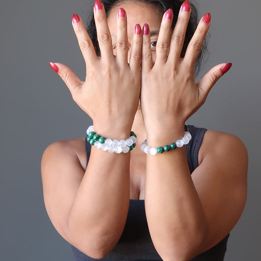 Sheila Satin of Satin Crystals shows off two of her custom design white selenite and green malachite crystal bracelets
