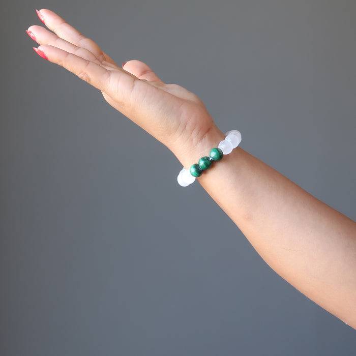 White selenite and green malachite round beaded bracelet on a hand model