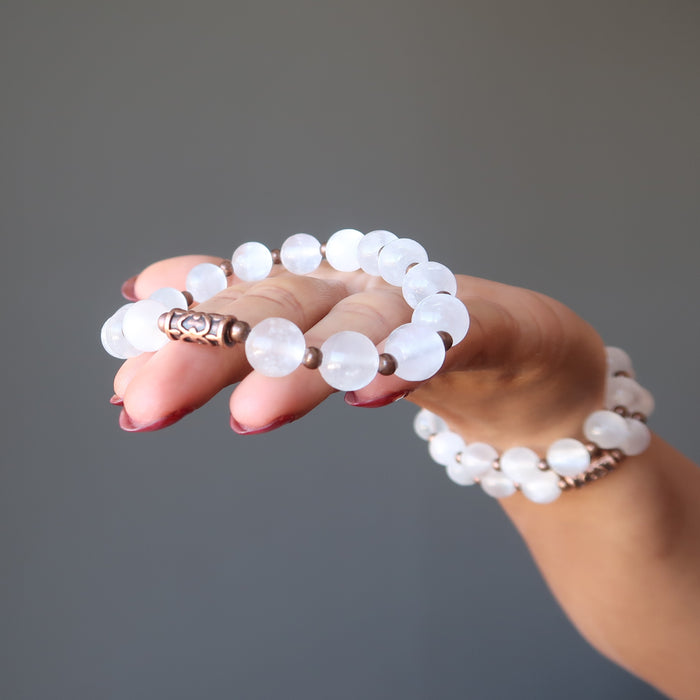 hand holding and wearing white selenite and antique beads stretch bracelet